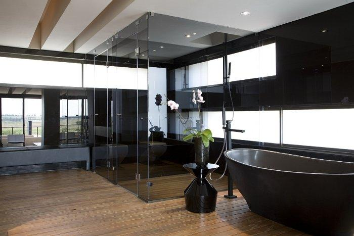 Luxurious bathroom design in black with bathtub and shower cabin