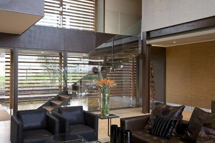 Luxurious living room with modern staircase made of glass and wood
