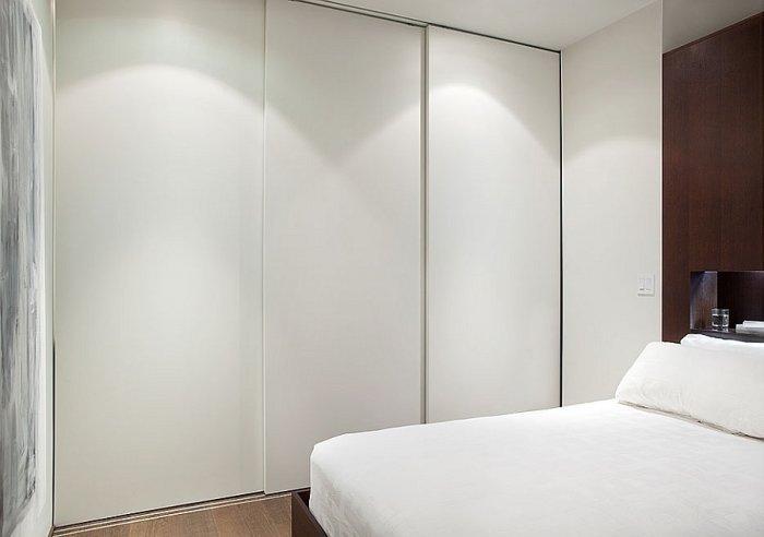 Modern bedroom with elegant lines and white sliding doors