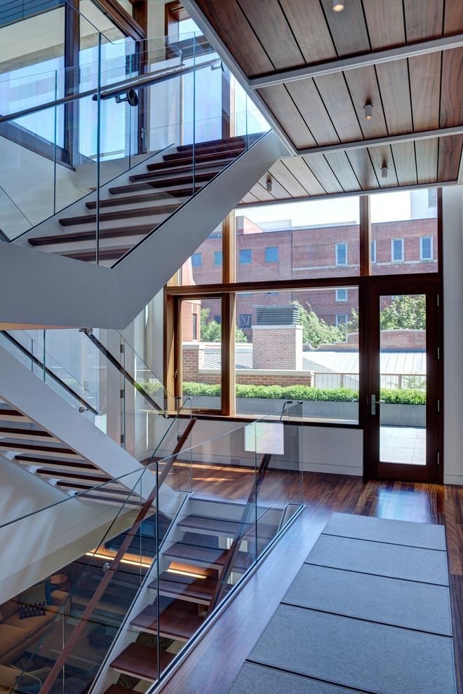 Modern staircase with wooden treads and glass railings connect the three levels