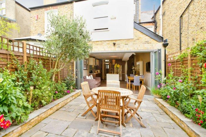 Open Kitchen With Luxurious Patio Furniture Outside In The Garden