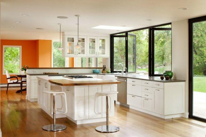 Open kitchen with white island and orange wall