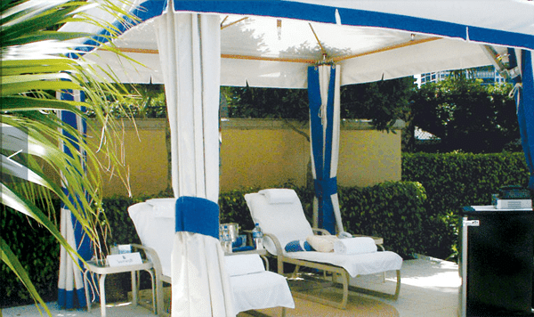 Outdoor canopy gazebo with white and blue curtains and comfortable lounge chairs