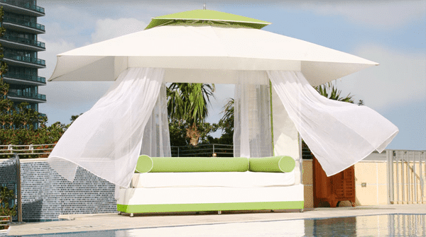 Outdoor canopy gazebo with white curtains and beautiful green accents