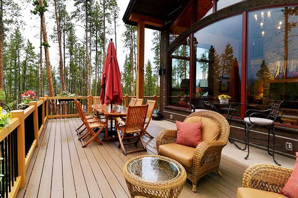 Outdoor dining area placed on the veranda of a luxurious house in the forest