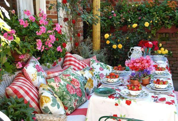 Outdoor dining area with long table and table cloth with a lot of flowers