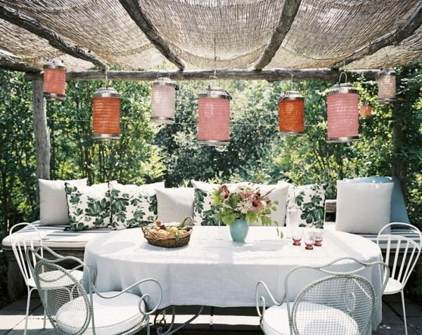 Outdoor dining room placed under a shelter and decorated with lanterns