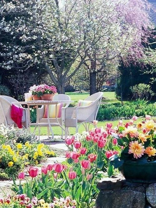 Outdoor dining set in a romantic garden with a lot of tulips and yellow flowers