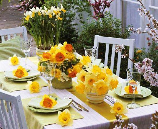 Outdoor dining table decorated with yellow flowers and prepared for lunch