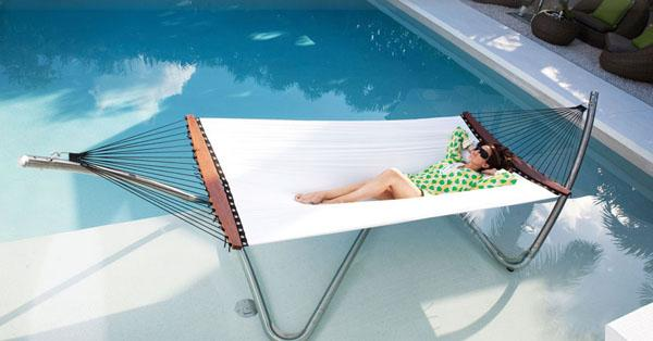 Outdoor lounge hammock near luxurious swimming pool with crystal blue waters