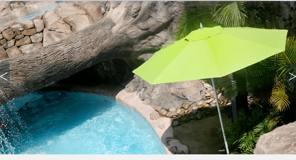 Outdoor relaxing area with green umbrella and blue waters