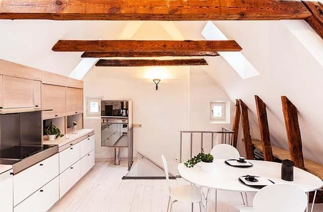 Scandinavian dining room with white walls and barn beams on the ceiling