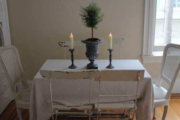 Small dining table with two vintage chairs and candles on the table