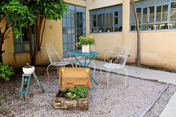 Small yard with vintage white chairs and small blue coffee table