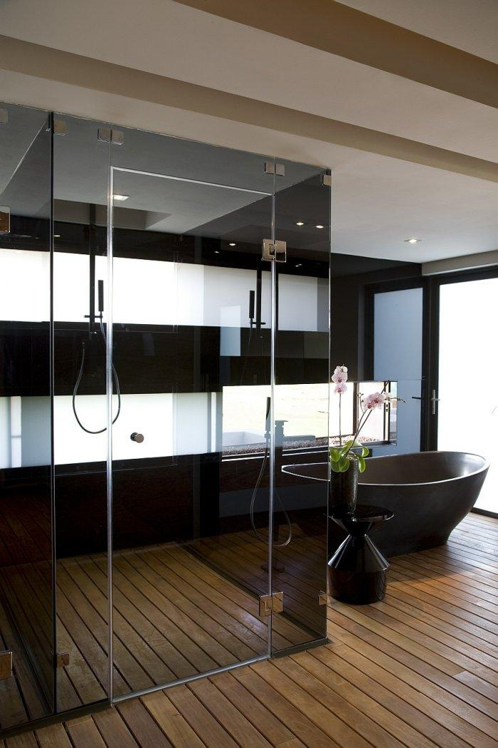 Very luxurious minimalist bathroom design with shower cabin and bathtub in dark colors