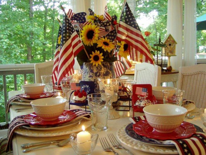 4th of July table with homemade centerpiece with American flags and sunflowers