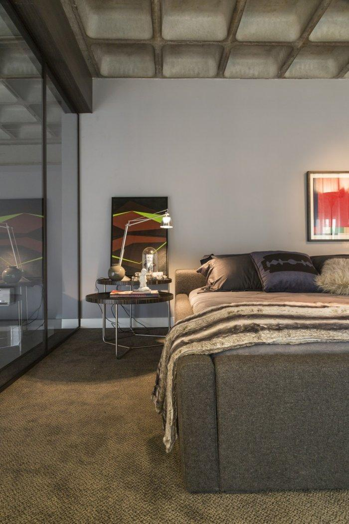 Abstract painting and bed inside a modern loft in Brazil