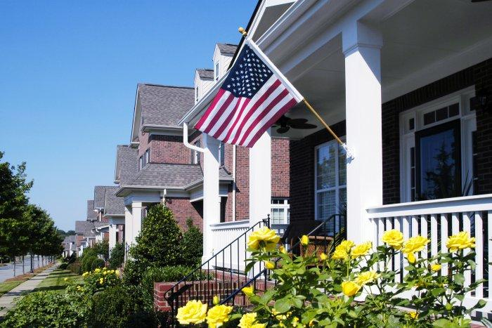 American flag on the front porch of a house in white