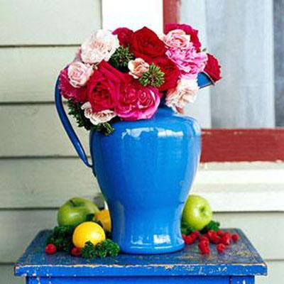 Colorful flowers inside a blue porcelain pitcher placed at the front porch