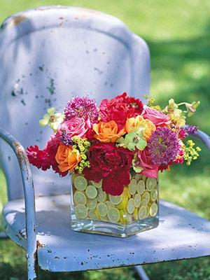 Colorful fresh flowers inside a glass vessel full of citruses