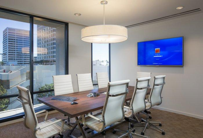 Conference room interior with table, chairs, TV screen and urban view