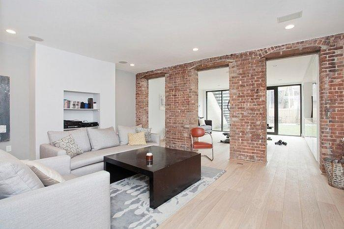 Eclectic living room in white with brick wall