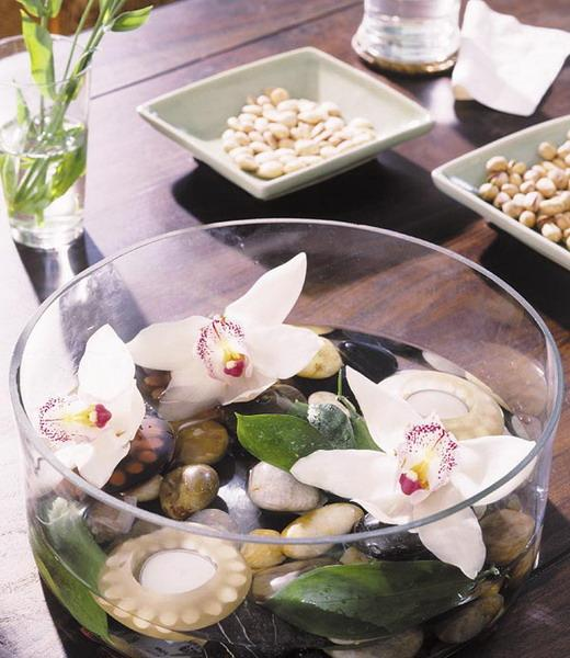 Flowers and pebbles inside a glass bow placed as a table centerpiece