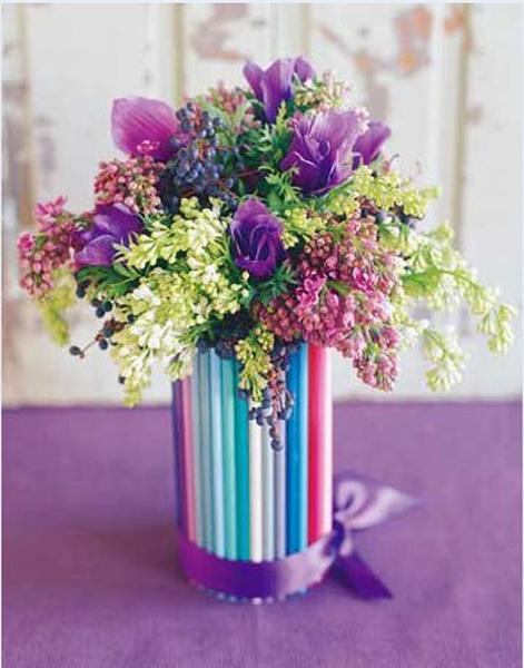 Fresh spring flowers with colorful straws in a tall glass