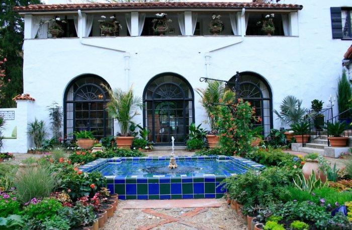 Garden in Mediterranean style with a swimming pool of two-colored mosaic tiles