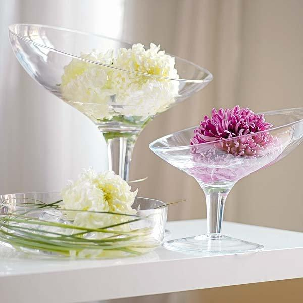 Gentle flowers placed in champagne glasses on a small home table