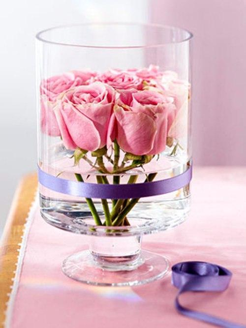 Gentle pink roses in an elegeant high glass ried with a silk ribbon