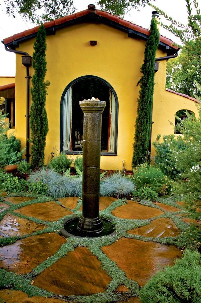 Mediterranean fountain in a garden with decorative flowers and yellow house facade