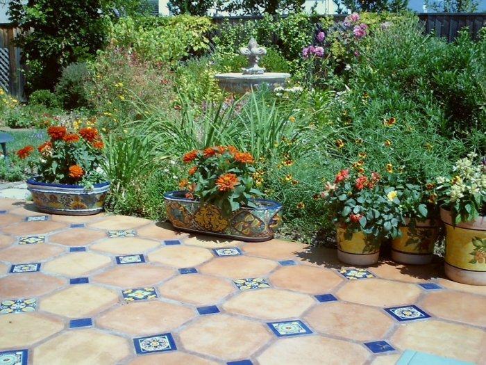 Mediterranean mosaic tiles used as garden decoration among beautiful summer flowers