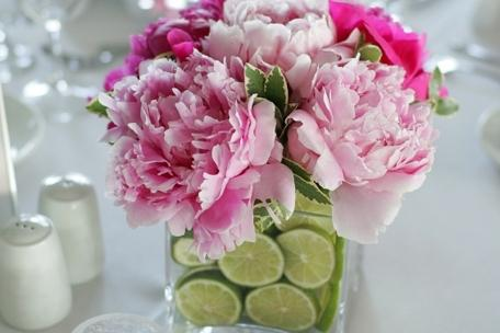 Pink flowers inside a glass vessel full of water and citruses