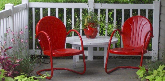 Red chairs form a lounge zone in the porch for 4th of July
