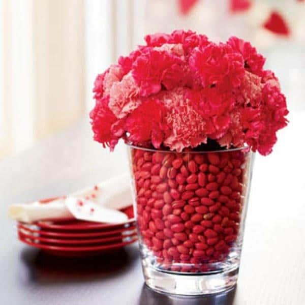 Red flowers and hip fruits inside a high glass used at the dinner table