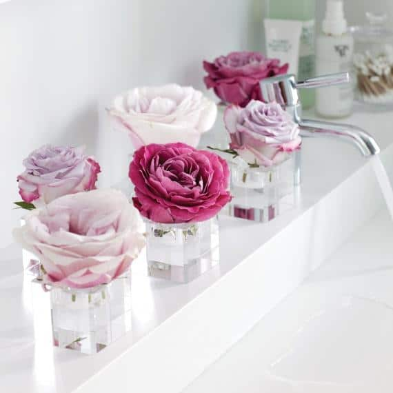Romantic roses in small candleholders on a bathroom shelf