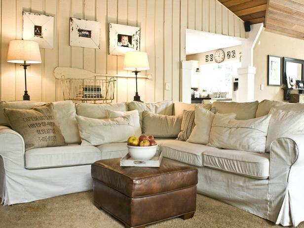 Shabby chic living room with white slipcovered sofa and vintage leather stool
