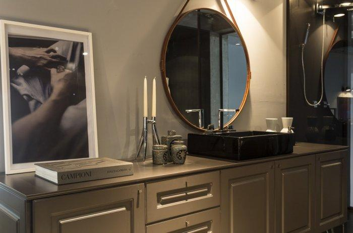 Traditional cabinets and big round mirror in the contemporary bathroom