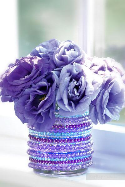 Violet flowers in a vessel decorated with purple and violet beads