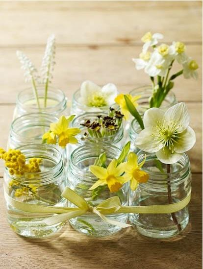 Yellow flowers in jars placed on the floor of a beautiful home