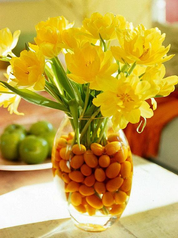 Yellow flowers inside a glass jar full of water and corn for decoration