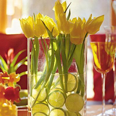 Yellow tulips inside a glass vessel full of water and citruses