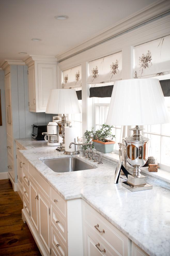 Beautiful white kitchen with marble countertops and windows in front of the sink