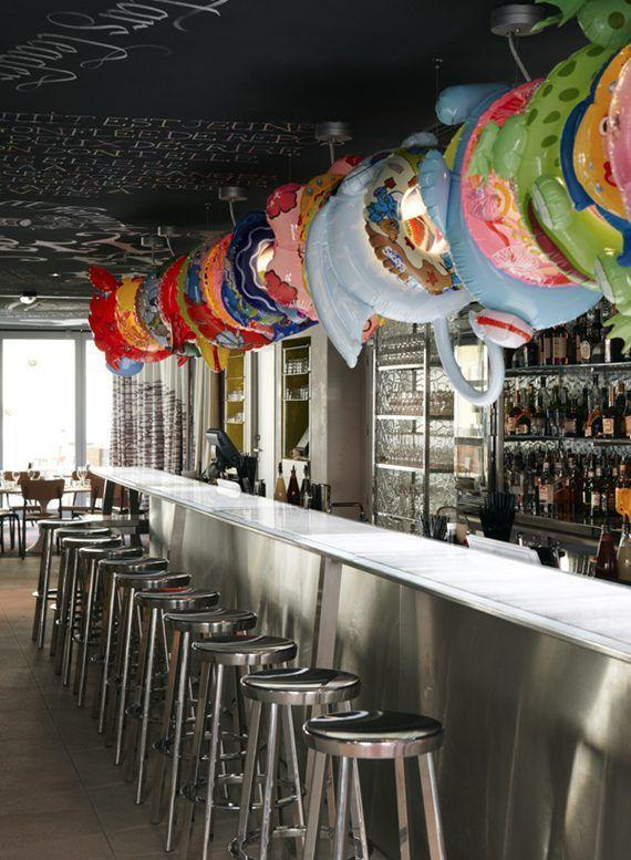 Cafe with funny baloons and long bar with stools