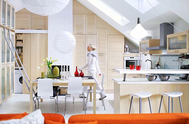 Contemporary white kitchen with orange accents in a flat