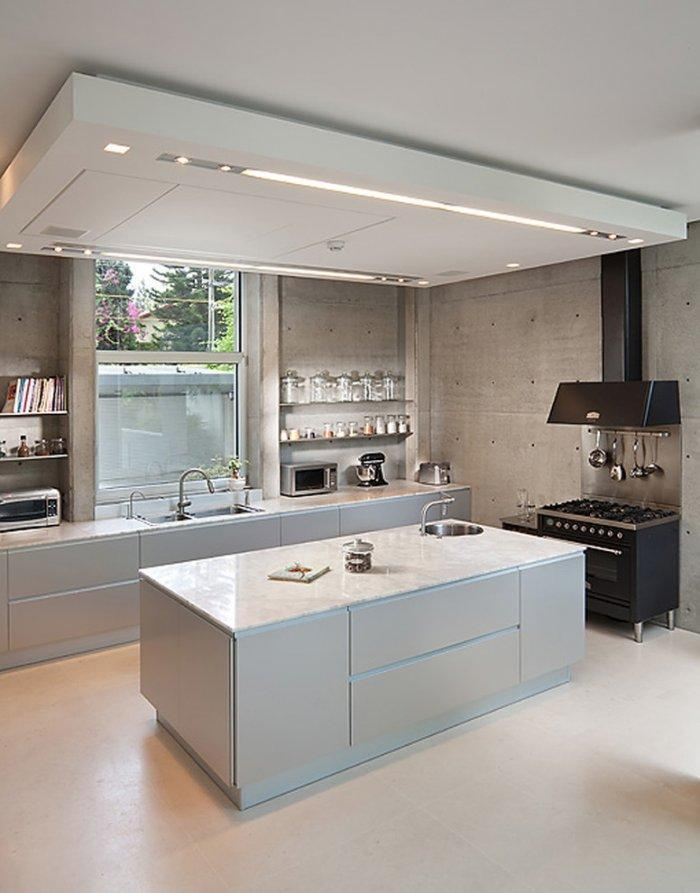 Elegant and stylish white kitchen with huge island in the middle