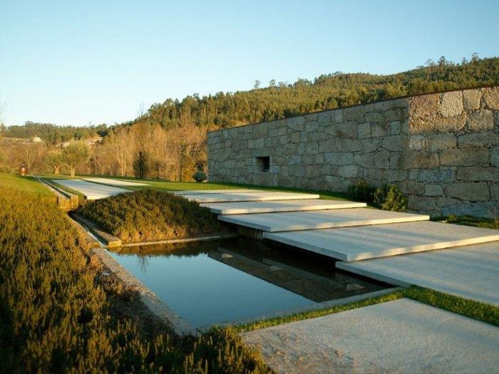 Giant concrete pavers half covereing a minimalist pond