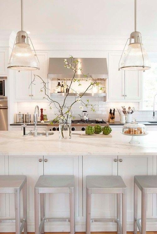 Huge white kitchen island with modern pendants above it