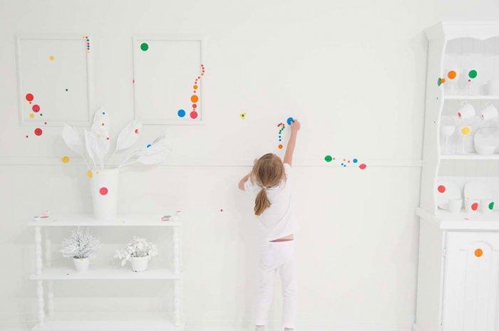Little girl placing colorful stickers on a white wall